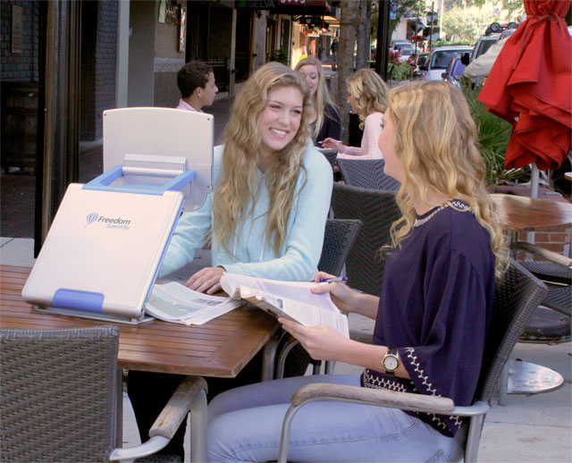 Students at an outdoor cafe using the TOPAZ PHD to study