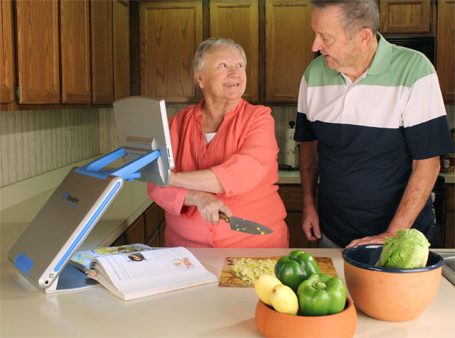 Woman and man preparing a meal while using the TOPAZ PHD to magnify a recipe in a cookbook